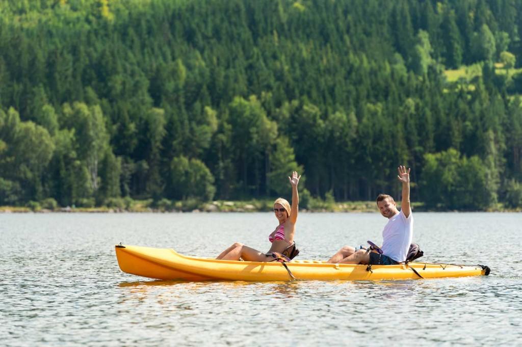 Ett par paddlar i en kanot och vinkar