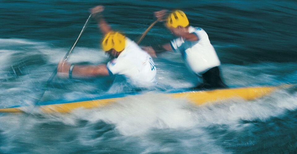 Två män paddlar i strömt vatten